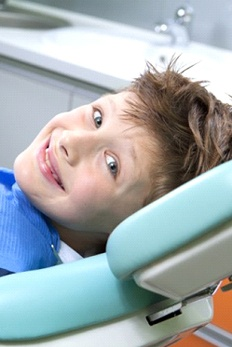 A young child giving a thumbs-up in a dental office.