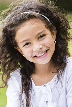 young girl with curly hair smiling