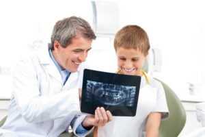 dentist showing child an x-ray
