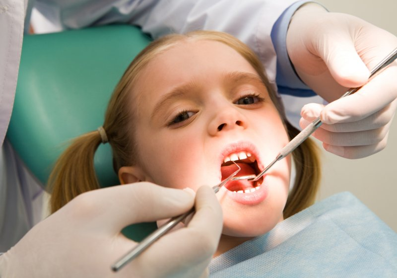 a young girl getting her teeth cleaned