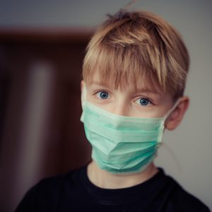 Boy wearing mask at pediatric dentist in Greenfield.